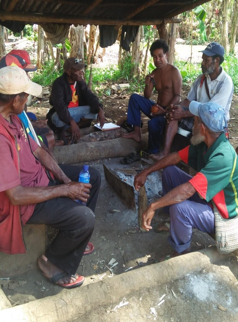 linus, shirtless and in blue trousers, mutually discussing issues with settlers at old Itikinumu rubber plantation, Sogeri-Koitaki valley, Central Province, Papua New Guinea, July 2018. Photo credit: Alfred Faiteli, Demography Division, University of PNG.